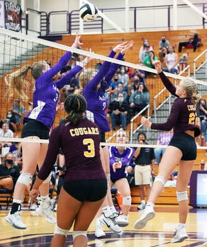 Bloomington North's Mia Robbennolt (22) hits the ball over the net as teammate Kyla Kante (3) looks on and Bloomington South's Cadance Ast (left) and Olivia Shields attempt to block. North and South could play again if they win their sectional openers.