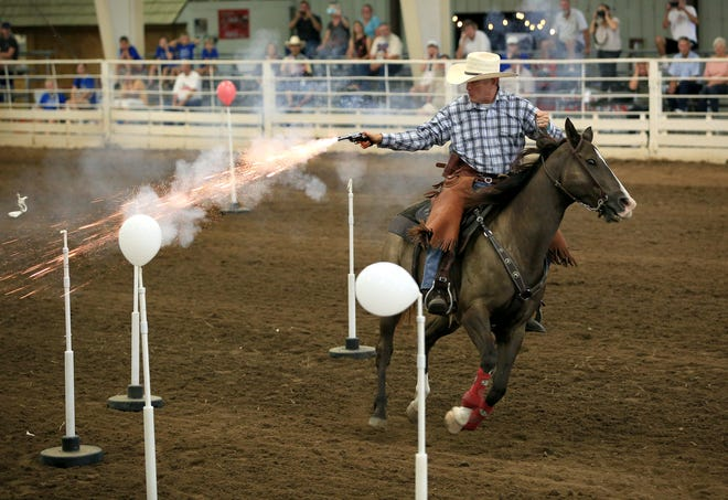 Scott Vanderhoofven, on his horse Moon, shoots balloons with black powder blanks during a demonstration of  Cowboy Mounted Shooting Tuesday morning in the Expo I building at the Kansas State Fair.