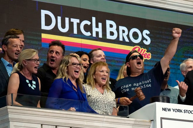 Dutch Bros Coffee Co-founder and Executive Chairman Travis Boersma, right, leads a chant before ringing the New York Stock Exchange closing bell, Wednesday.