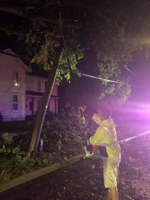An employee with Dundee Department of Public Works helps remove a tree that fell onto a power line following a storm that passed through Monroe County Tuesday night.