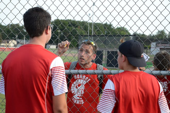 Monroe tennis coach Stephen Reau gives his No. 3 doubles team of Zane Johnson a pep talk during a 4-4 tie with Bedford Tuesday.