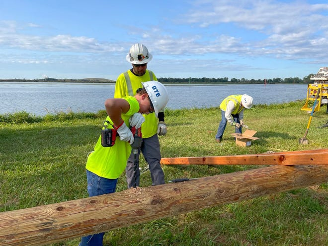 Chase Cousino drills into the utility pole that will hold his osprey platform. Also pictured are DTE employees Jason Barnett and Clayton Elton.