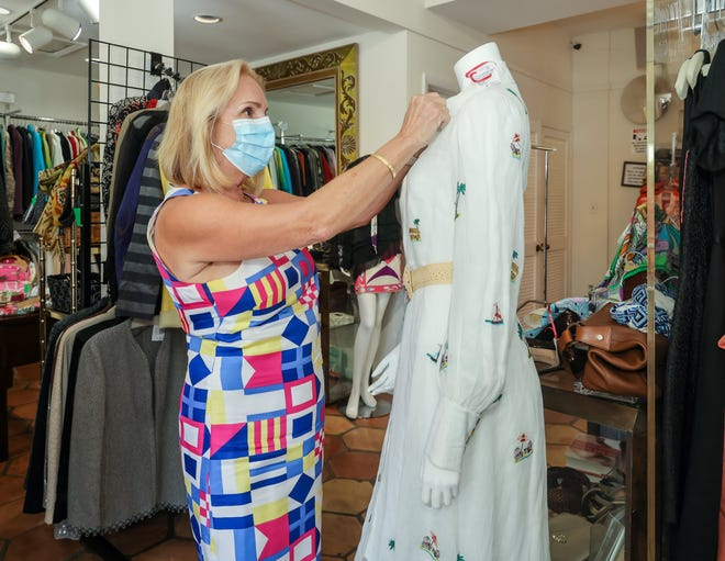 Church Mouse retail assistant Laurie Kasprzyk arranges a Zimmerman white embroidered linen dress on a mannequin Sept. 14. The dress retails for $1,200, but is listed at $495 in the store.