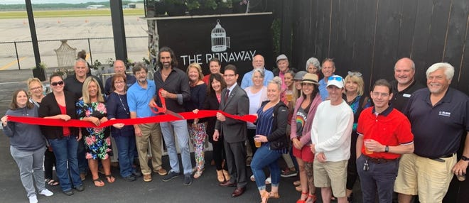 Pictured cutting the ribbon (l-r):Rick Stanley, President of the Sanford Springvale Chamber of Commerce, Dan Bowden, Owner of the Runaway and Pilots Cove Café and Eleanor Vadenais, President of the Wells Chamber of Commerce.