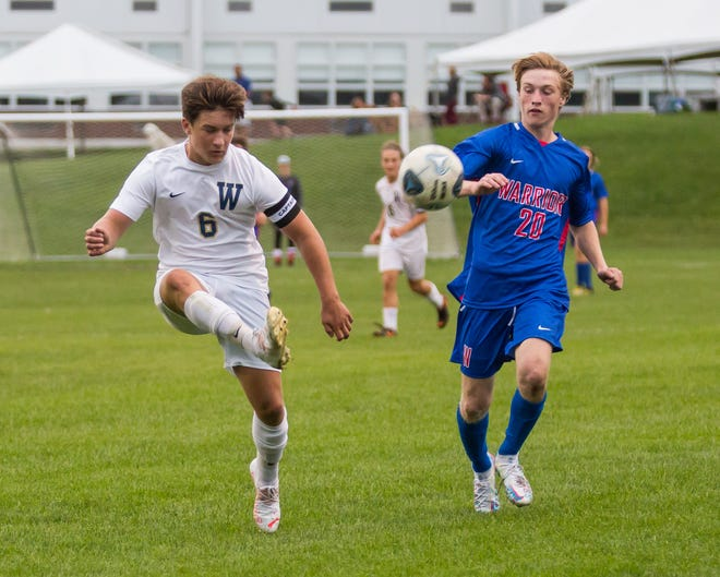Winnacunnet's Williem Belanger, right, defends against a touch by Windham's Ryan Husson during Tuesday's Division I boys soccer game in Hampton. Windham won 2-0.