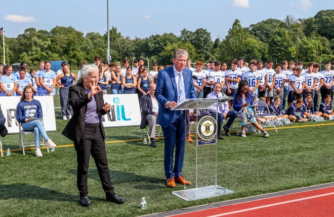 Gov. Dan McKee took his semiweekly coronavirus briefing on the road again this week, here addressing the crowd on a Johnston High School athletic field. A host of state and local officials — and a student — exhorted the gathered teenagers to get vaccinated if they haven't done so.