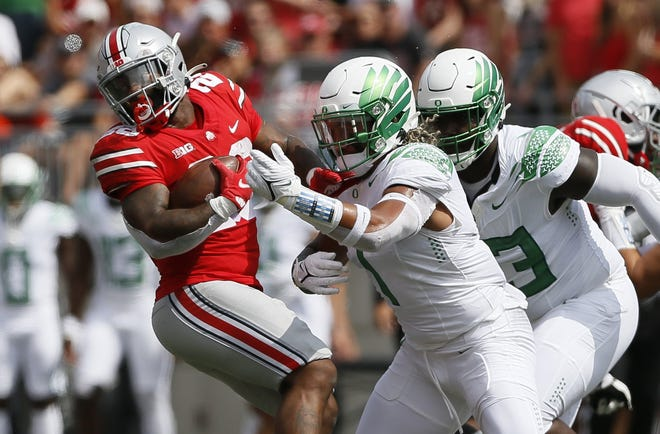 Ohio State Buckeyes running back Miyan Williams, left, spins away from Oregon linebacker Noah Sewell (1) during the first half of the Ducks' 35-28 win over the Buckeyes.