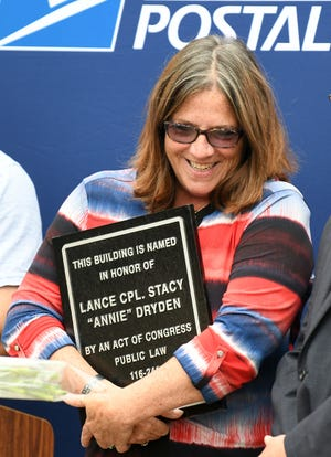 """Thea Dryden holds a plaque during a dedication ceremony Wednesday to rename the North Canton post office for her daughter Marine Lance Cpl. Stacy """"Annie"""" Dryden who died in 2008 while serving in Iraq."""