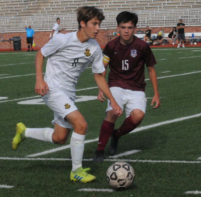Salina South's Carson Crow (11) dribbles the ball while being defended by Salina Central's Ben Kraft (15) during Tuesday's match at Salina Stadium.