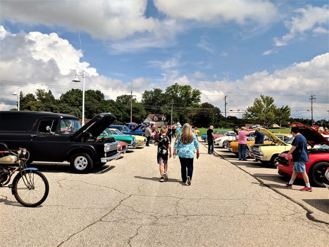 People check out the cruise-in during the village of Lakemore's centennial celebration.