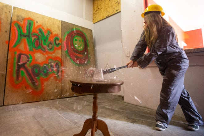 Carrie Correll, owner of The Havoc Room, smashes a glass vase as she demonstrates what patrons can expect to do once The Havoc Room opens.