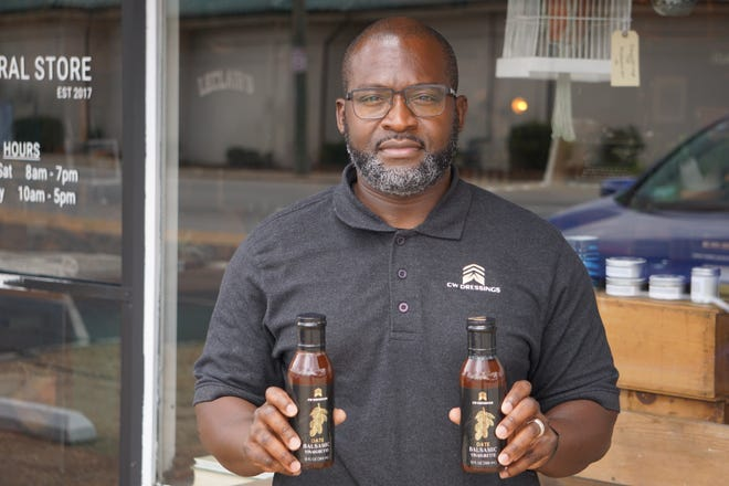 Chris Whitehurst, founder of CW Dressings, holding his product outside LaClair's General Store in Fayetteville, one of around 10 stores that carry his date balsamic vinaigrette dressing.
