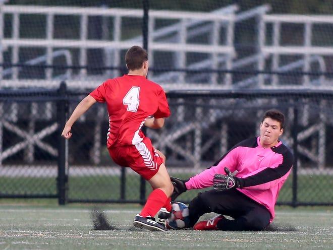 Silver Lake goalie Boyd Wechter goes to block the shot of Hingham's Sam Benham.