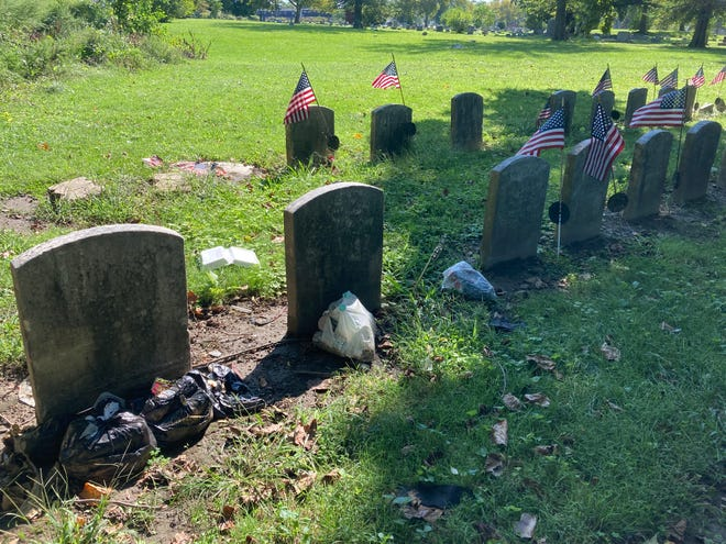 Trash bags and other debris are left next to veterans' graves in New Camden Cemetery.