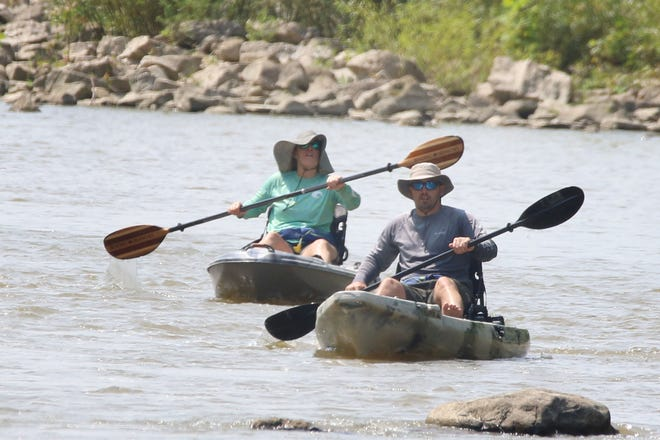 Kayakers take a leisurely trip down the Sandusky River, at River Cliff Park, on a summer Saturday.
