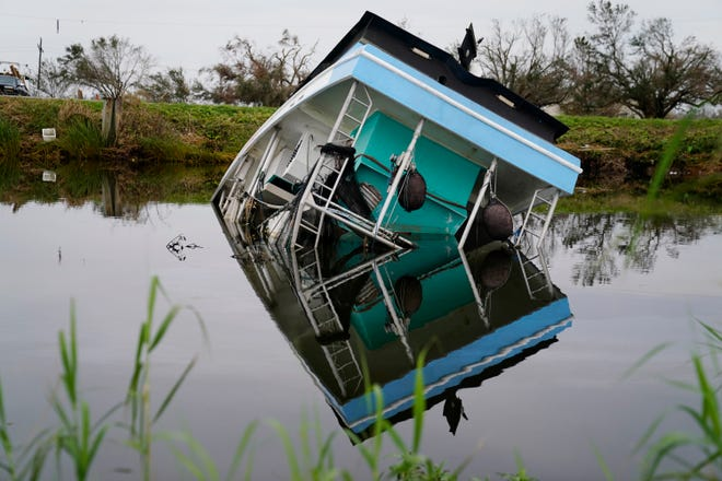 A shrimp boat is seen flipped over in bayou waters near Cut Off Wednesday, Sept. 9, 2021, after Hurricane Ida created widespread damage in the area.