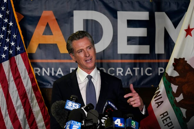 California Gov. Gavin Newsom addresses reporters at the John L. Burton California Democratic Party headquarters in Sacramento, Calif., on Tuesday, Sept. 14, 2021, after beating back the recall that aimed to remove him from office.