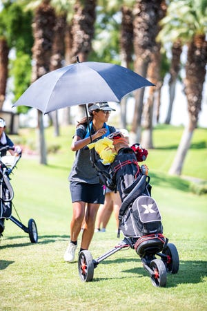 Madison Siva of Xavier Prep uses a sun umbrella and wears a wet towel around her neck to stay cool prior to golfing against Palm Desert High School at JW Marriott Desert Springs Resort in Palm Desert, Calif., on September 14, 2021.
