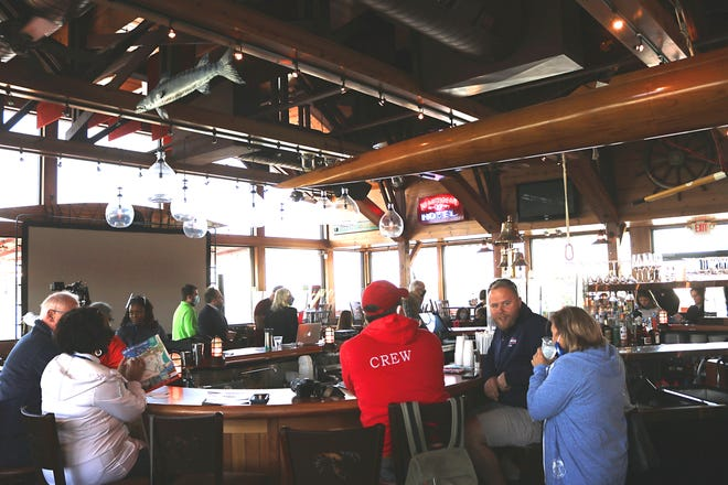 Patrons sit around a bar at the Boardwalk restaurant early into this year's summer tourism season, one of many local businesses at Put-in-Bay bouncing back despite difficult circumstances amid the ongoing COVID-19 pandemic.