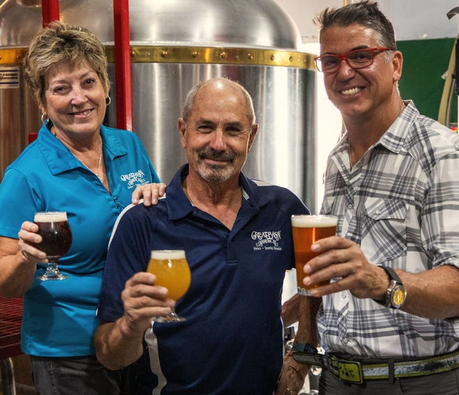 Great Basin Brewing Company owners Tom and Bonda Young raise a toast with Mark Estee, right, Local Food Group CEO and restaurateur. Great Basin Brewing Co. announced they will merge with Local Food Group on Wednesday, Sept. 15.