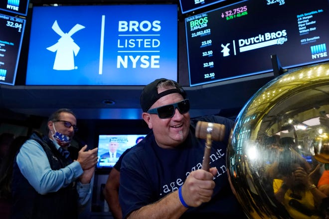 Dutch Bros Coffee Co-founder and Executive Chairman Travis Boersma rings the ceremonial first trade bell on the floor of the New York Stock Exchange, as his company's IPO opens, Wednesday. (AP Photo/Richard Drew)