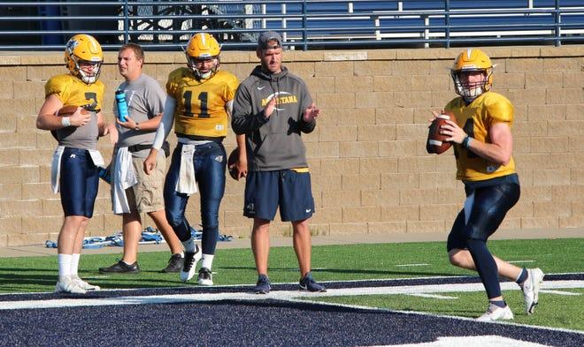 Augustana quarterback Carter Robinson runs through a drill while offensive coordinator James Schrenk and Kyle Saddler (11) watch.
