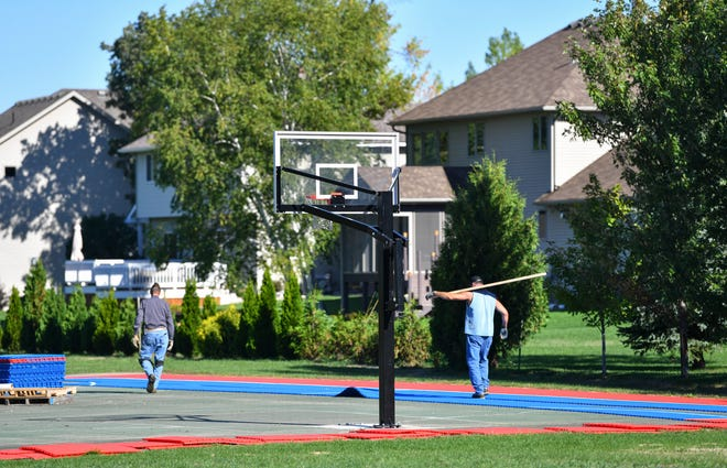 Workers remove the surface tiles on the basketball court Wednesday, Sept. 15, 2021, at The Wilds park in Sartell.