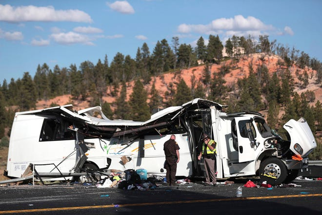 FILE - In this Sept. 20, 2019, file photo, authorities work the scene of a tour bus crash near Bryce Canyon National Park in Utah. The families of Chinese tourists killed or injured in the crash say the state's design and maintenance failed to keep the remote highway safe. (Spenser Heaps/The Deseret News via AP, File)