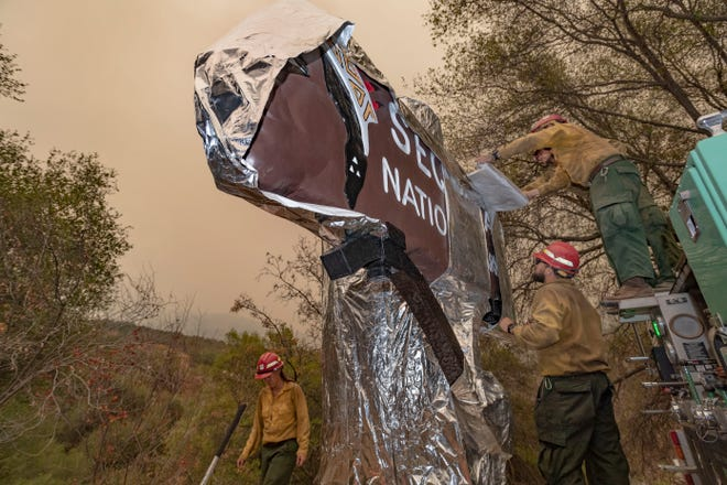 Firefighters from New Mexico wrap Sequoia National Park's iconic entrance sign on Tuesday, September 14, 2021. The spread of the KNP Complex Fire has closed the park and put areas of Three Rivers are under evacuation warnings and orders. The sign, restored in recent years, has been at the entrance since 1935.