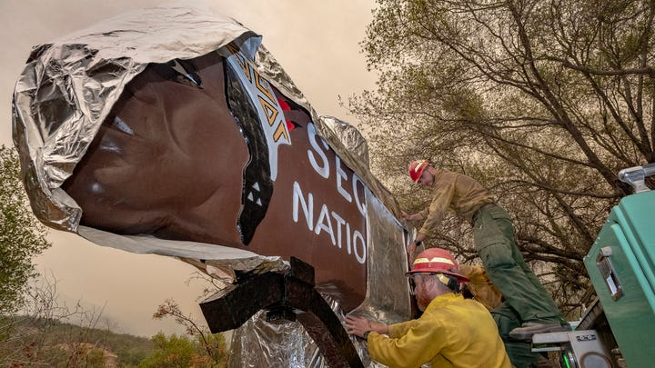 Firefighters from New Mexico wrap Sequoia National Park's iconic entrance sign on Tuesday, September 14, 2021. The spread of the KNP Complex Fire has closed the park and put areas of Three Rivers under evacuation warnings and orders. The sign, restored in recent years, has been at the entrance since 1935.