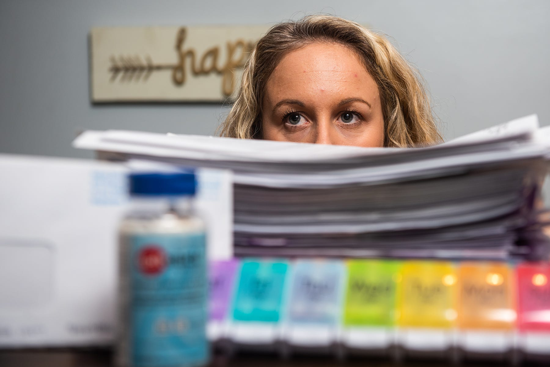 Caitlin Barber peeks over the stack of paperwork that she has amassed since her COVID-19 diagnoses in 2019 as she sits for a portrait at her home in Saugerties, NY on Wednesday, July 28, 2021. Barber caught COVID-19 while working at a nursing home in 2019, she's now fighting for workers compensation. Kelly Marsh/For the Times Herald-Record