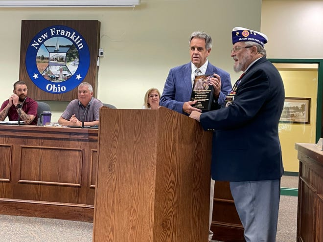 Larry Emery, commander of the Military Order of the Purple Heart, Chapter 699, presents New Franklin Mayor Paul Adamson with a Purple Heart city plaque Wednesday as City Council members watch.