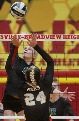 Nordonia's Celine Puscian hits the ball over Brecksville's Haylee Hebron during the Bees' volleyball victory over the Knights on Wednesday night. [Mike Cardew/Beacon Journal]