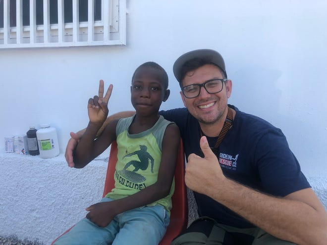 Brock Mayer with a child after the earthquake in Haiti last month.