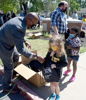 Columbia Public Schools Assistant Superintendent De'Vion Moore, left, and Parkade Elementary School library media specialist Josh Howard hand out bags with books to Parkade students Thursday at a Read Across Columbia Heart of Missouri United Way event.