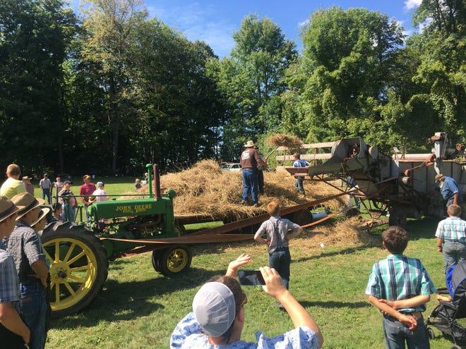Howard Leach, of Dresden, teaching a crew of Mennonite boys during the hay threshing demonstration.