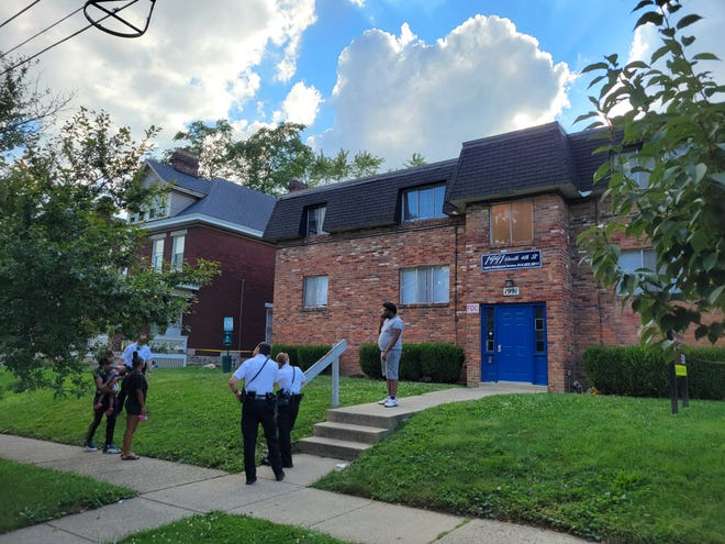 Columbus police speak to residents near an apartment complex that was the scene of a fatal shooting Thursday afternoon in the University District.