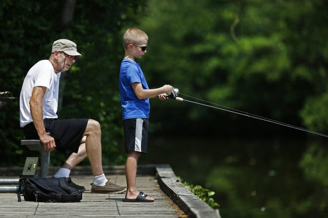 In this file photo, Dan Potter gives his grandson, Kayce, 8, fishing advice as he fishes Tuesday, June 7, 2020, at Sharon Woods Metro Park. They are from Johnstown.
