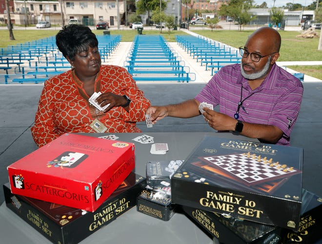 """Daytona Beach City Commissioner Paula Reed and City Manager Deric Feacher play a game of cards to warm up for the city's inaugural """"game night' at Daisy Stocking Park. The event is Saturday night, and any adult who likes games is invited. Note: Bring your own games."""