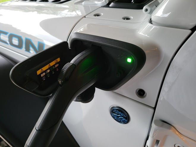 A new Jeep Wrangler plug-in hybrid charges up at a home charger.