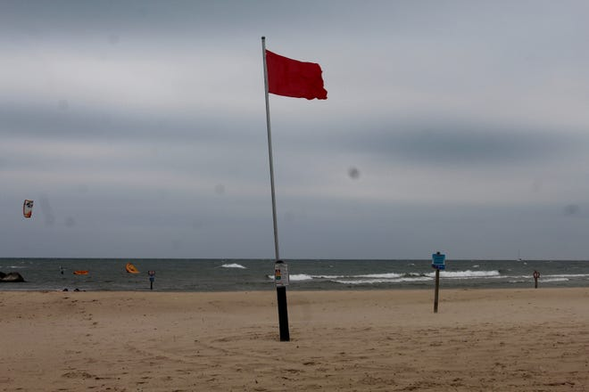 A red flag flies on the beach during a windy day at Holland State Park on Wednesday, Aug. 11, 2021, in Park Township, Mich. Starting in May 2022, swimming at Michigan state parks on red flag days will be banned and punishable by a fine up to $500.