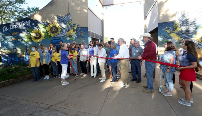 Marcy Kauffman sets up the ribbon-cutting event with Governor Laura Kelly in front of the new mural by artist Brady Scott at the Kansas State Fair Friday morning, Sept. 16, 2021.