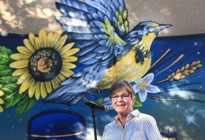 Governor Laura Kelly talks to people in front of the new mural painted by Brady Scott on the Visit Hutch Visitor Information Booth at the Kansas State Fair Thursday morning.