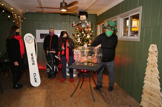 Bill Arnold of Bayside Distributing LLC picks the winner of the White Claw themed tree at Shooter's Pub on Dec. 3, 2020.  Also pictured are Lisa Lortie, Karen Drapaniotis and Bonnie Galinski.