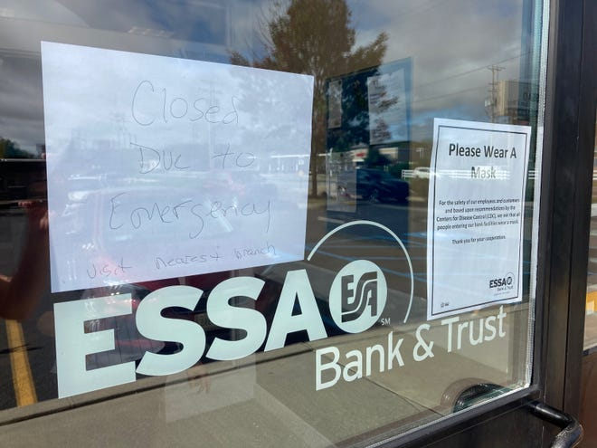 """A sign posted to the front door of East Stroudsburg Savings Association Bank & Trust  in Marshalls Creek urges customers to """"visit nearest branch"""" and that the branch would be closed """"due to emergency."""" The bank was the scene for a reported robbery Thursday morning."""