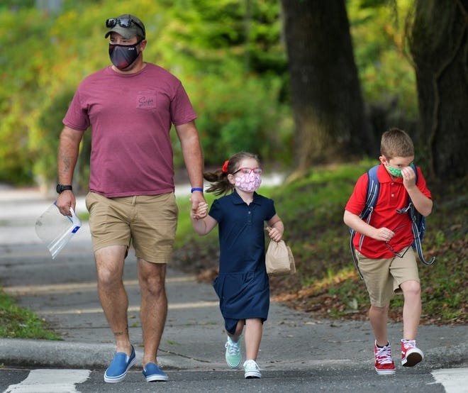 Dad Brandon Wilson walks with his children Braelynn, 6, and Braedy, 8, to Beauclerc Elementary School on the first day of classes for Duval County Public Schools during the pandemic last school year. (The Florida Times-Union/TNS)