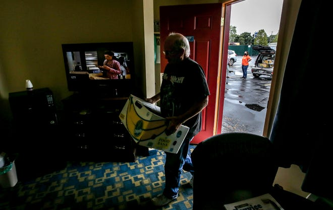 Paul Crowley brings a care package into his room at the Rumford Motor Inn while We Share Hope's Johanna Corcoran, in orange, waits in the parking lot to distribute more food.