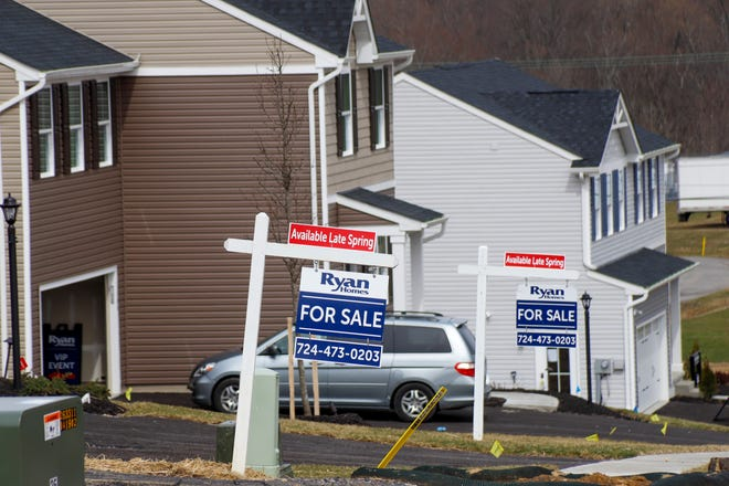 Model homes and for sale signs line the streets as construction continues at a housing plan in Zelienople, Pa., Wednesday, March 18, 2020. U.S. home sales jumped in February to their highest level in 13 years, a trend that will almost certainly be reversed as the viral outbreak keeps more people at home.  (AP Photo/Keith Srakocic) ORG XMIT: NYBZ704