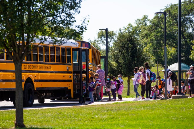 Students get onto buses Thursday at Monroe Primary Center in South Bend.