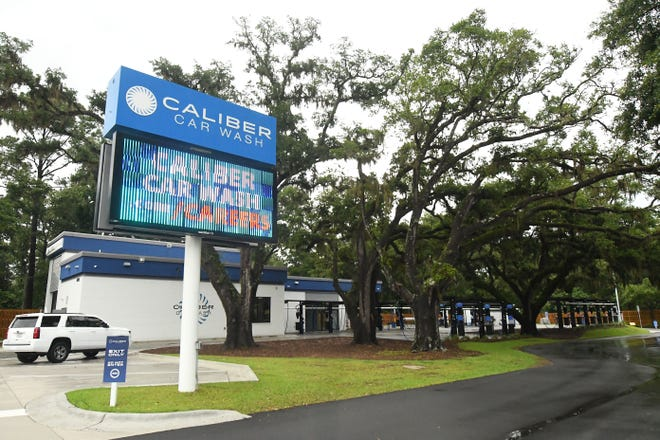 Caliber Car Wash off of Market Street in Wilmington is tucked back among old oak trees that were preserved when building the site. Many locals have expressed concern about how to balance new development with tree preservation more broadly in the Cape Fear region. [KEN BLEVINS/STARNEWS]